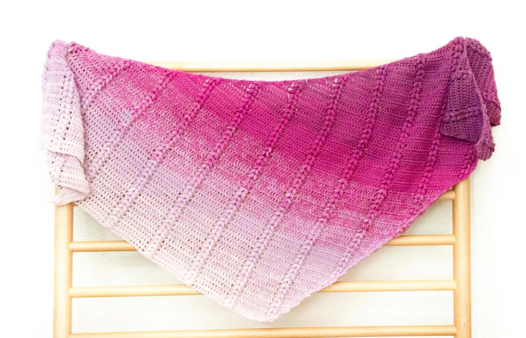blackberry pudding shawl on a wooden rack