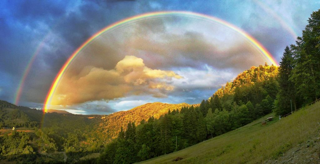 Full double rainbow over mountains in Romania