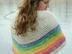 Rainbow crochet shawl worn around the shoulders and tied at the back, showing off the beautiful colors