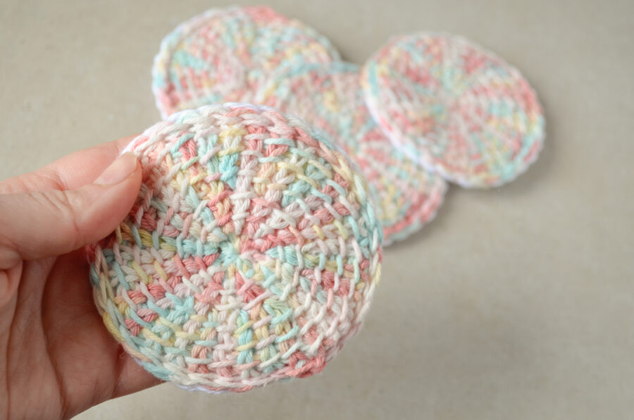 Front view of a Tunisian crochet face scrubby versus a pile of other scrubbies