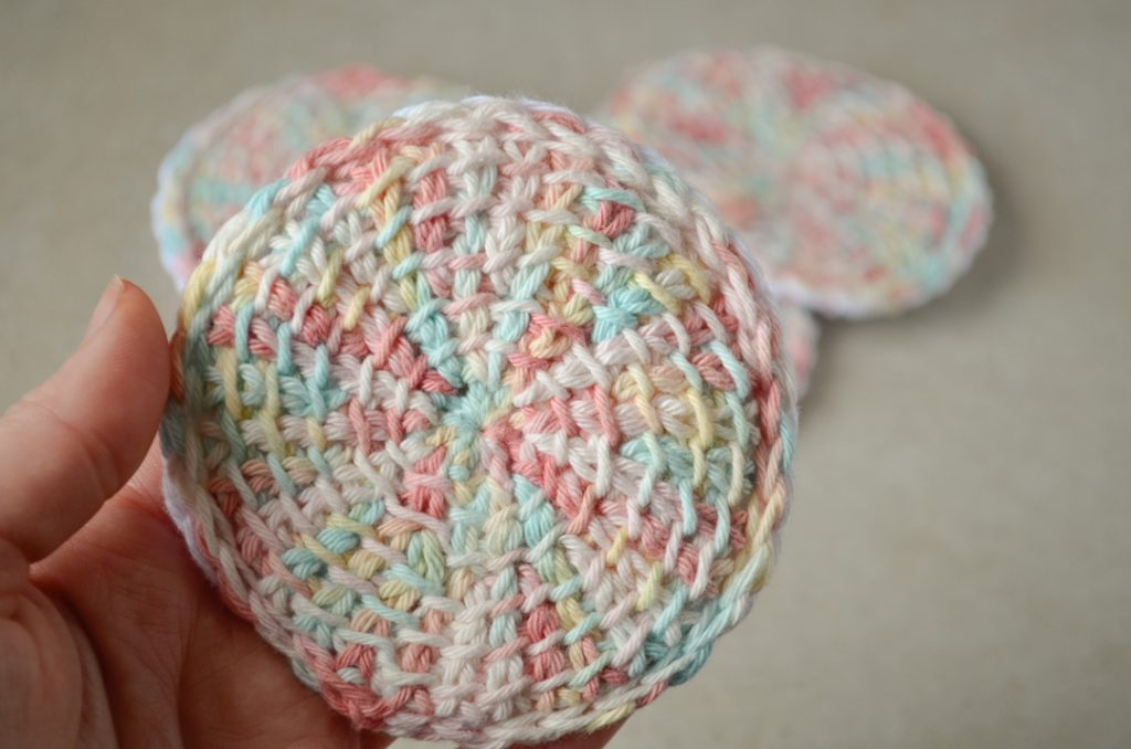 Front view of a Tunisian crochet face scrubby versus a pile of similar scrubbies