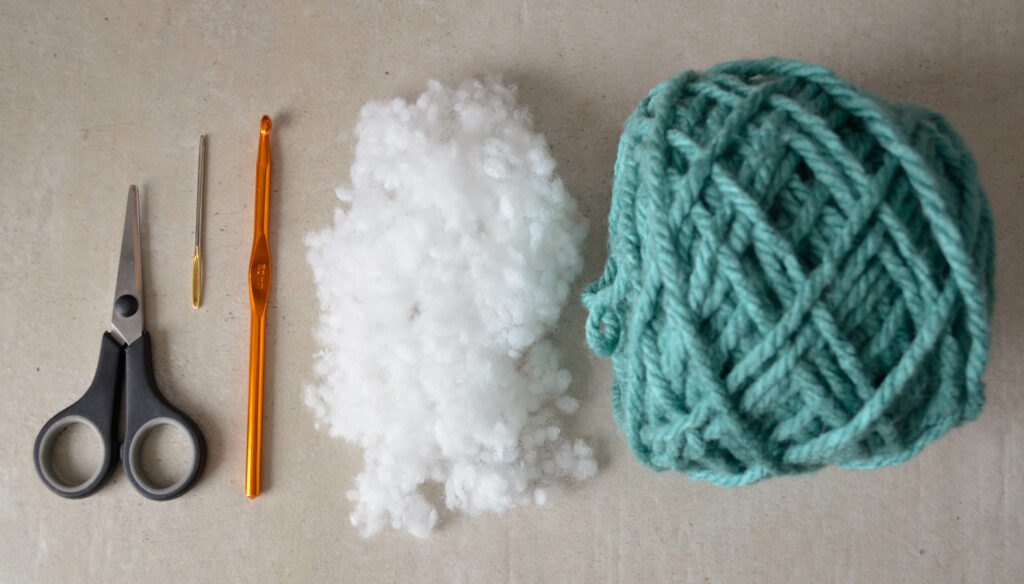 Materials for the crochet fidget toy, from left to right: scissors, tapestry needle, hook, stuffing, yarn