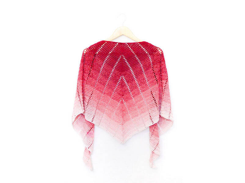 Raspberry croissant shawl on a hanger showing the back view or the spine of the shawl