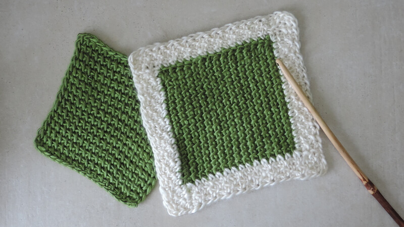 Tunisian crochet squares, one blocked, one with a non-curling border, plus a hook