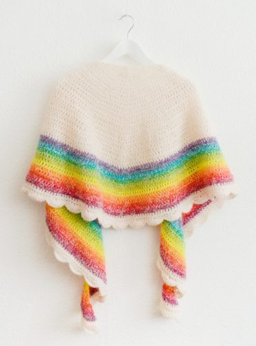Crocheted rainbow shawl on hanger